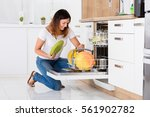 Stock photo happy young woman arranging plates in dishwasher at home 561902782