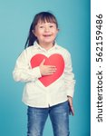 Small photo of Sweet little girl with Down Syndrome, playing with paper heart