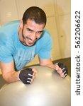 Small photo of Fitball abdominal push ups Swiss ball man one single leg pushup at fitness gym