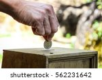 a man hand putting coin into a... | Shutterstock . vector #562231642