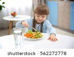 small girl eating vegetables in ... | Shutterstock . vector #562272778