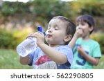 little kid drinking water | Shutterstock . vector #562290805