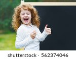 laughing little girl showing... | Shutterstock . vector #562374046