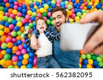 cheerful joyful son and dad... | Shutterstock . vector #562382095