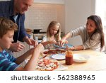 family at home in kitchen... | Shutterstock . vector #562388965