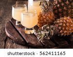 pineapple slices and juice in... | Shutterstock . vector #562411165
