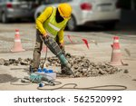Male worker with full safety equipments drilling and repairing concrete driveway surface with jackhammer ,danger sign area. Professional worker. - stock photo
