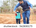 father training small toddler... | Shutterstock . vector #562830175