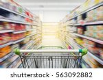 Small photo of Supermarket aisle with empty green shopping cart