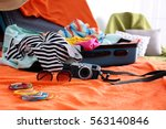 open suitcase with clothes and... | Shutterstock . vector #563140846