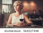 elegant blonde lady with glass... | Shutterstock . vector #563227348