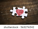 Stock photo closeup of two pieces of a puzzle forming a heart on a rustic wooden surface depicting the idea of 563276542