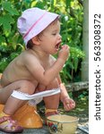 Small photo of Little happy Caucasian girl sitting outdoors on a potty-chair, piddling, eating berries and enjoying on nature background.