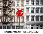 Small photo of Stop sign in front of historic old buildings with windows and fire escape at the intersection of Howard and Mercer Streets in Lower Manhattan, New York City NYC