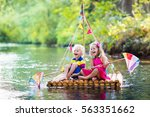 two children on wooden raft... | Shutterstock . vector #563351662