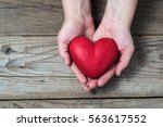 red hart on palms   love symbol | Shutterstock . vector #563617552
