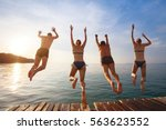 group of friends jumping to the ... | Shutterstock . vector #563623552