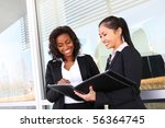 Two interracial (african and asian) business women team at office building - stock photo