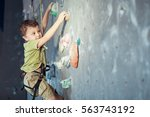 little boy climbing a rock wall ... | Shutterstock . vector #563743192