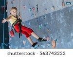 little girl climbing a rock... | Shutterstock . vector #563743222