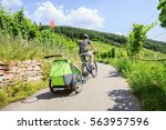 young parent cycling through... | Shutterstock . vector #563957596