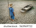 Small photo of Global warming, Children with boat on cracked earth after the climate change