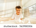 cute boy awaking in white... | Shutterstock . vector #563980306