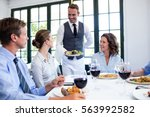waiter serving salad to the... | Shutterstock . vector #563992582