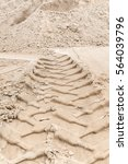 Small photo of Wheel tracks of construction machines in the sand; Building site; Building sand for road construction or landscaping; Construction sector; Fine aggregate