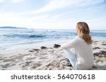 Woman Sitting On The Beach In...