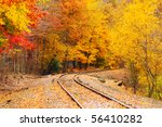 An old railroad track (still in use) runs through a brilliantly colored autumn woods - stock photo