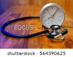 stethoscope and clock on wooden ... | Shutterstock . vector #564390625