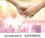 Small photo of lover hands holding together on de-focused of pink flowers in garden with little vintage houses , family , help and support concept