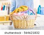Small photo of Woman holding wicker basket with clean clothes