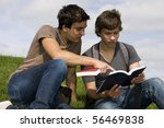 Two teenager students sit on the grass reading a book - stock photo