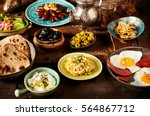 Small photo of Moroccan Algerian breakfast table. Vintage background with different plates with delicious traditional middle eastern food