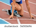 Female athlete in starting position on an athletic track - stock photo