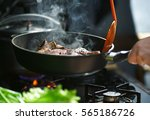 Man Cooks Meat In A Frying Pan