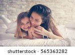 Small photo of Mother and daughter enjoy in bed at home and looking at the camera.