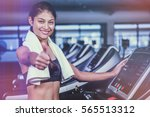 smiling fit woman showing... | Shutterstock . vector #565513312