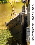 Small photo of An old viking ship anchored in the water by the dock stern tied to pier.
