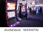 A slot machine is seen in a casino room with people playing other slot machines in the background. - stock photo