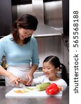 mother cutting vegetables ... | Shutterstock . vector #565568188