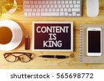 Small photo of Chalkboard written CONTENT IS KING on wooden desk with flare effect