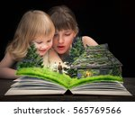 Small photo of The children delighted in watching a fairy tale on the pages of an open book. Tale characters - the old man and old woman. Rustic old house, a forest glade with flowers.