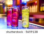 cocktail drinks on a bar, blurry bar background - stock photo