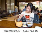 woman eating in japanese... | Shutterstock . vector #566076115