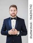 Small photo of Handsome man in tuxedo and bow tie looking at camera. Fashionable, festive clothing. emcee on grey background