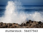 Blue Waves Crashing On A Rocky...