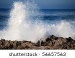 Blue Waves Crashing On A Rocky...